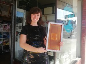 Woman standing out the front of a shop holding a screen printing frame