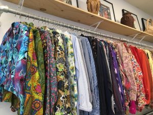Row of colourful patterned shirts in a 2nd-hand shop