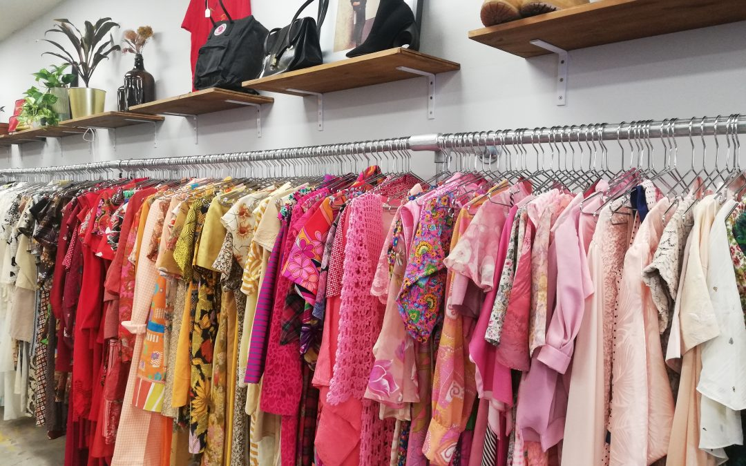 Row of colourful vintage dresses in a shop, with shoes on rack above