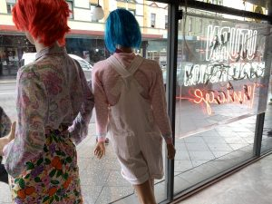 Two manikins in a shop window, taken from behind and name of shop UTurn