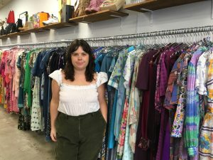 Woman standing in front of rows of colourful clothes in a 2nd-hand clothes shop