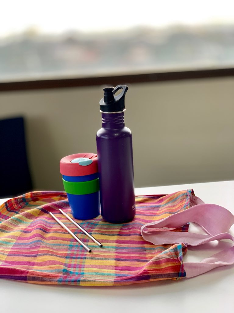 Reusable water bottle, coffee cup, bag and straw on desk