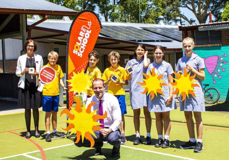Children and adults holding suns and standing in front of building with new solar panels