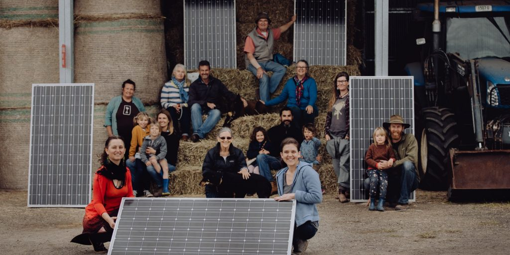 People in a barn holding solar panels