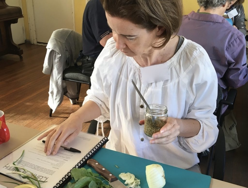 Photo of woman in a white blouse is sitting at a table holding a jar of spices and looking at a recipe. A chopping board with knife and fennel is in front of her. Other people sit behind her.