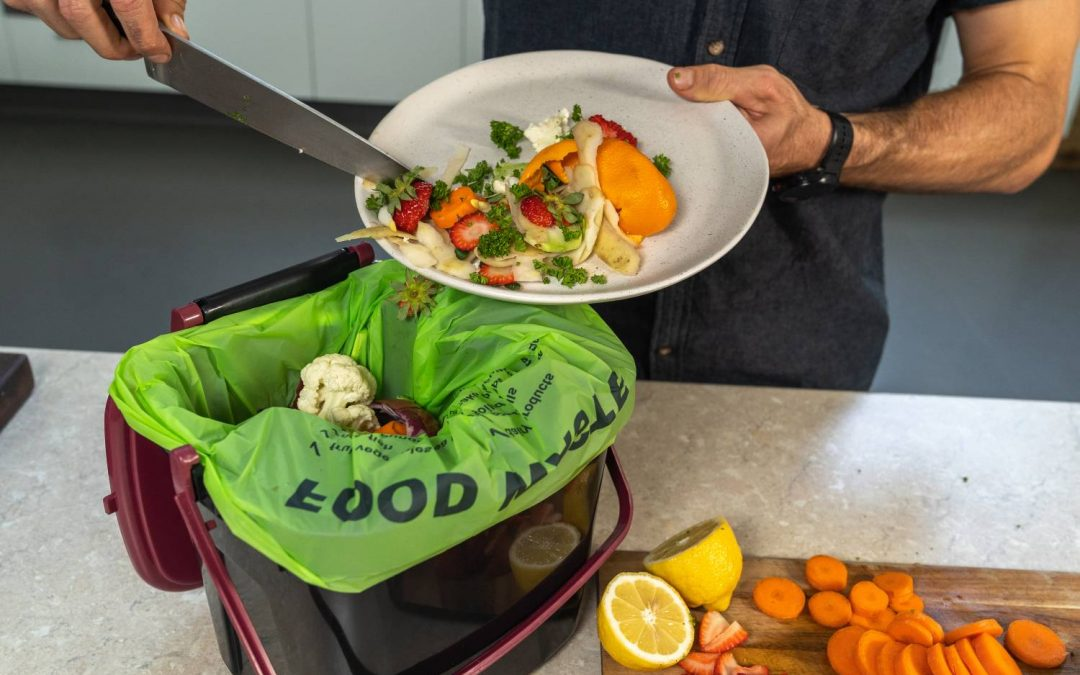 A photograph of a person scraping vegetable and fruit scraps from a white plate into a green bag that sits in aplastic container. Chopped up carrots, lemon and strawberries sit on a chopping board on the bench.